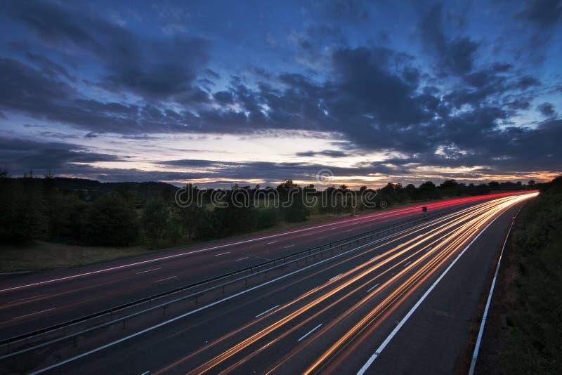 Leuchtespuren auf einer Autobahn an der Dämmerung stockfoto