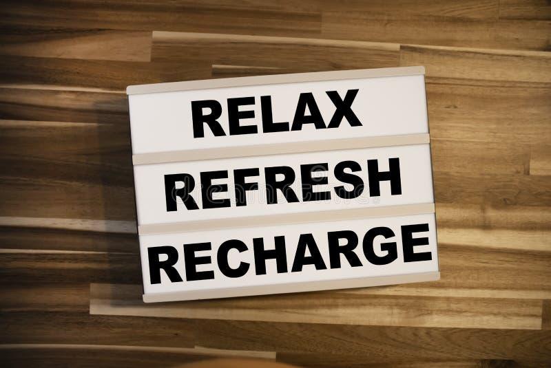 Leuchtpult oder Leuchtkasten mit der Meldung Reflex Refresh Recharge auf einem Holztisch lizenzfreie stockbilder
