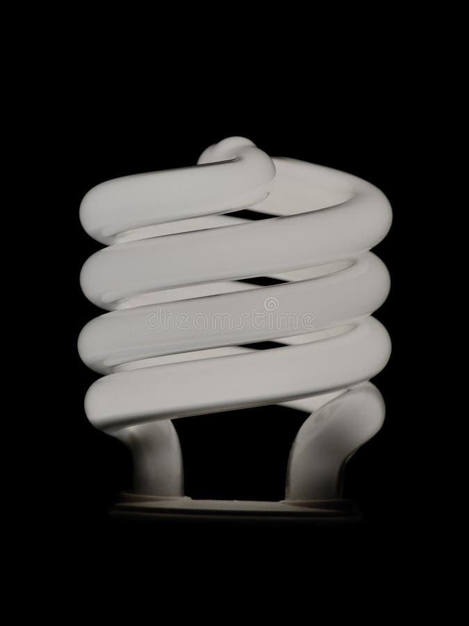 Leuchtstoffenergieeinsparungsspiralenlampe lokalisiert auf einem schwarzen Hintergrund lizenzfreies stockfoto