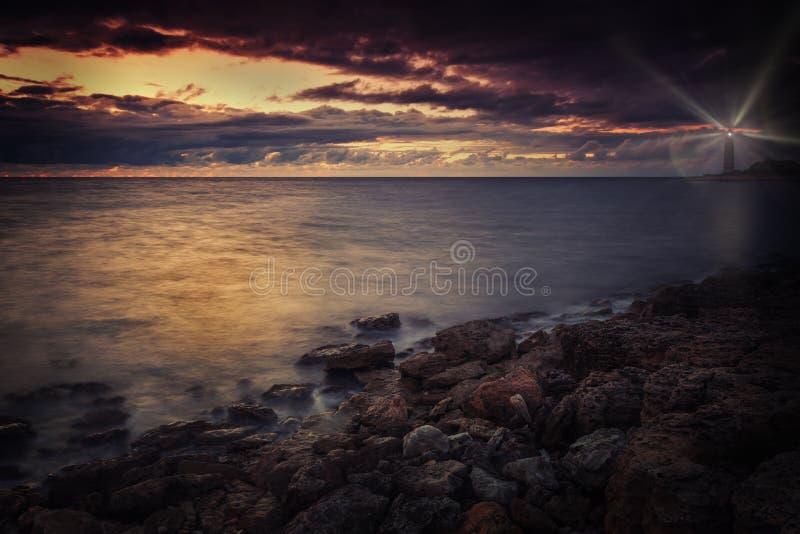 Leuchtturm auf der Küste nachts mit Strahlen des Lichtes stockbild