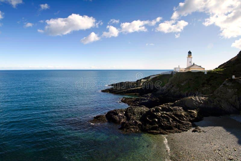 Leuchtturm auf Klippen mit Strand und Meer stockfoto