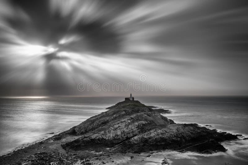 Leuchtturm auf Landspitze mit Sonne strahlt über Ozeanlandschaft mit lizenzfreie stockfotos