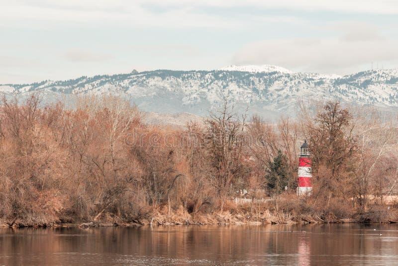 Leuchtturm in den Bäumen mit Schnee bedeckte Berge im Hintergrund mit einer Kappe stockbilder