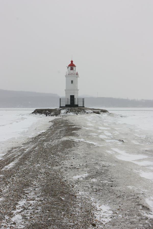 Leuchtturm im Winter an der Küste lizenzfreies stockbild