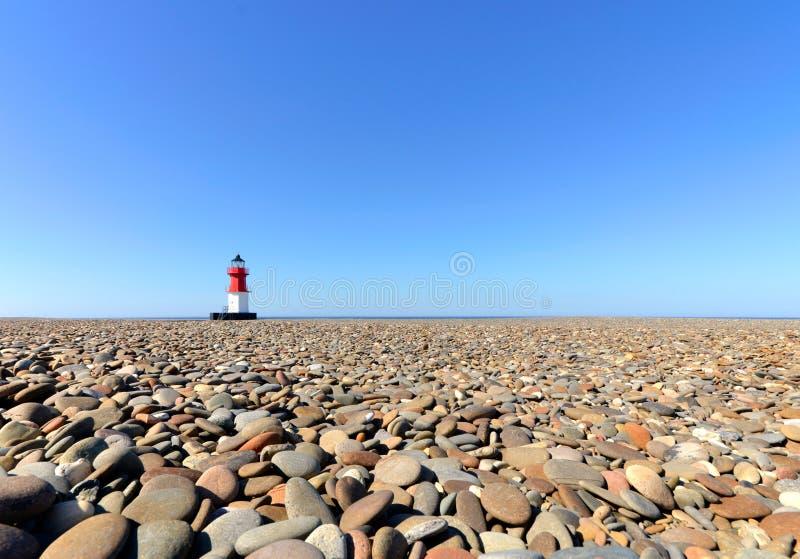 Leuchtturm mit Strand-Kieseln im Vordergrund lizenzfreies stockfoto