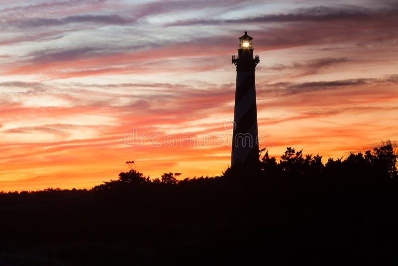 Leuchtturm-Schattenbild-Sonnenuntergang-Himmel stockfotos