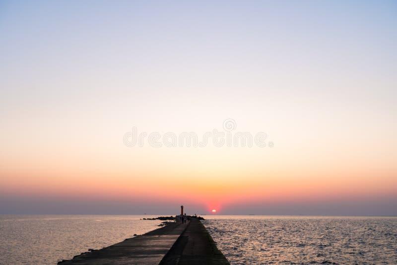 Leuchtturm w?hrend eines letzten des Sonnenuntergangs mit einer gro?en Sonne nah an dem Horizont und dem klaren Himmel lizenzfreies stockfoto