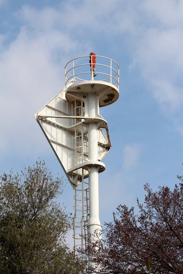 Leuchtturmleuchtfeuer-Warnlicht auf den starken Metallbau umgeben mit Sicherheitszaun und hohen Bäumen auf bewölktem blauem Himme stockfoto