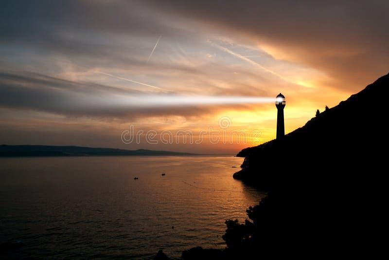 Leuchtturmscheinwerferstrahl durch Meeresluft nachts. lizenzfreies stockbild