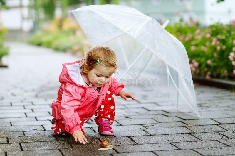 Leuk aanbiddelijk babymeisje die slak op een gang ontdekken Mooi krullend peuterkind die pret op regenachtige dag hebben Met groo stock foto's