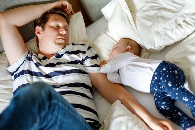 Leuk aanbiddelijk babymeisje van 6 maanden en haar vaderslaap vreedzaam in bed thuis royalty-vrije stock afbeelding
