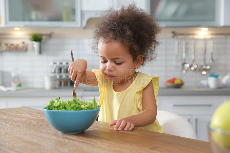 Leuk Afrikaans-Amerikaans meisje die plantaardige salade eten bij lijst royalty-vrije stock foto's