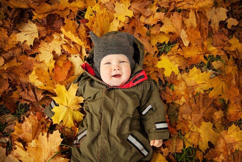Leuk Autumn Child op Dalings Gele Bladeren stock foto's