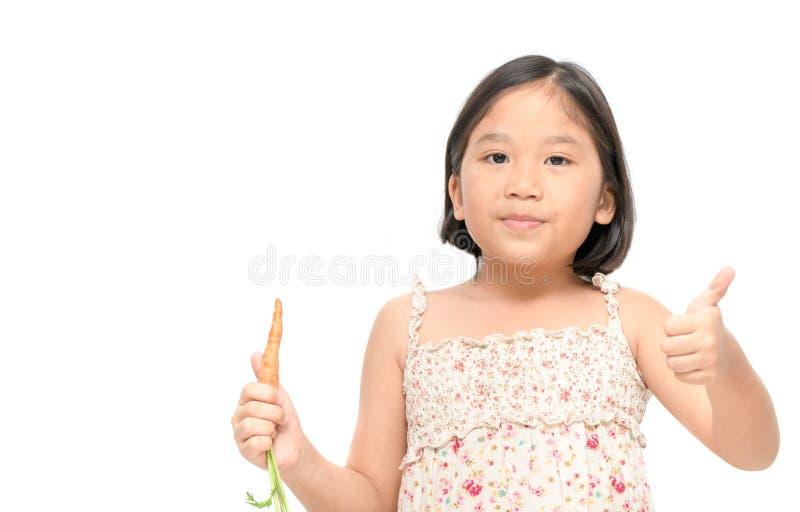 Leuk Aziatisch die meisje zoals babywortel op witte achtergrond wordt geïsoleerd stock foto's