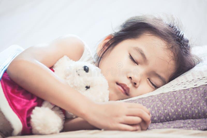 Leuk Aziatisch kindmeisje die en haar teddybeer slapen koesteren royalty-vrije stock afbeeldingen