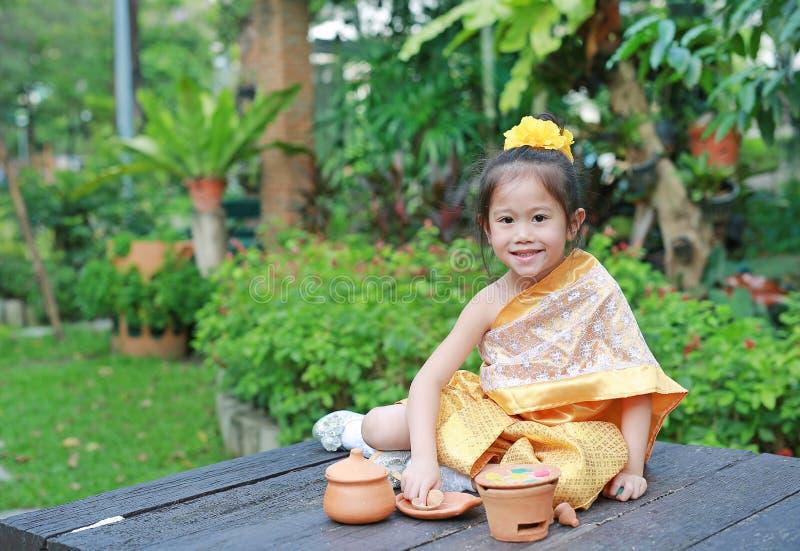 Leuk Aziatisch kindmeisje in traditioneel Thais kledingsspel die Thais cultuurdessert in de openbare tuin maken royalty-vrije stock foto