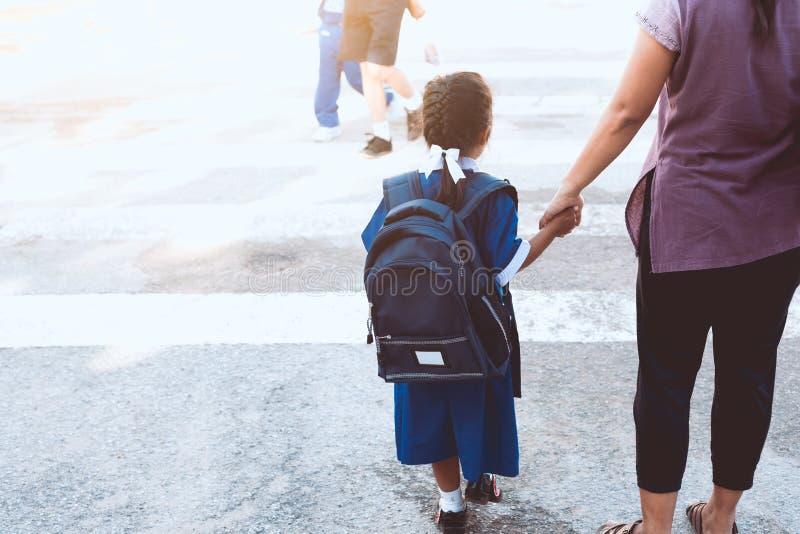 Leuk Aziatisch leerlingsmeisje die met rugzak haar moeder houden stock fotografie