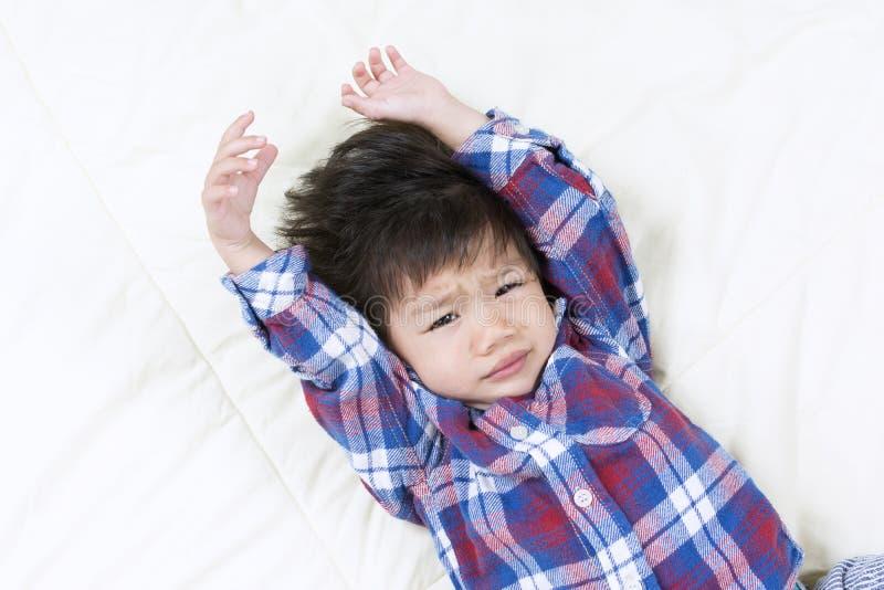 Leuk Aziatisch Little Boy-Kielzog omhoog op bed Met een slaperig gezicht stock afbeeldingen