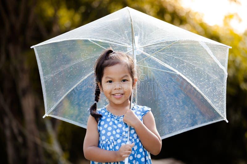 leuk Aziatisch meisje met paraplu in regen stock afbeeldingen