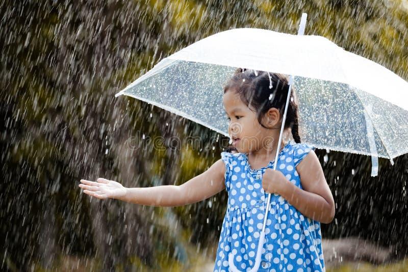 leuk Aziatisch meisje met paraplu in regen stock foto