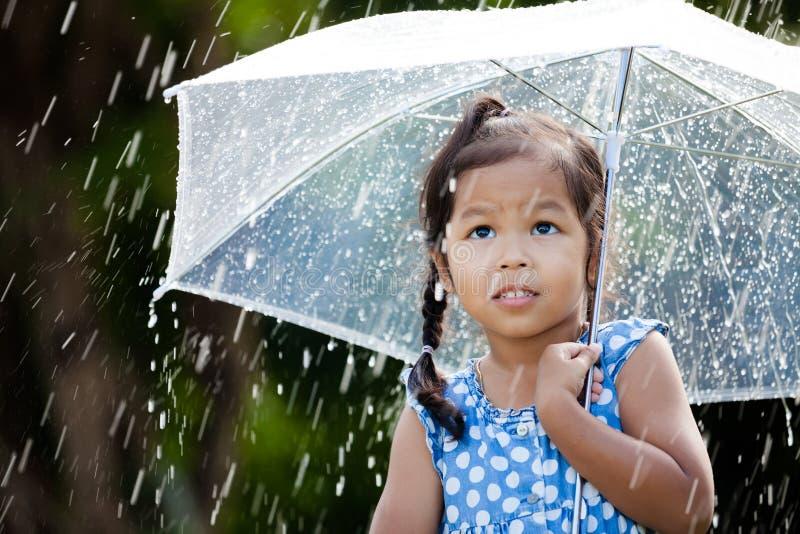 leuk Aziatisch meisje met paraplu in regen stock fotografie