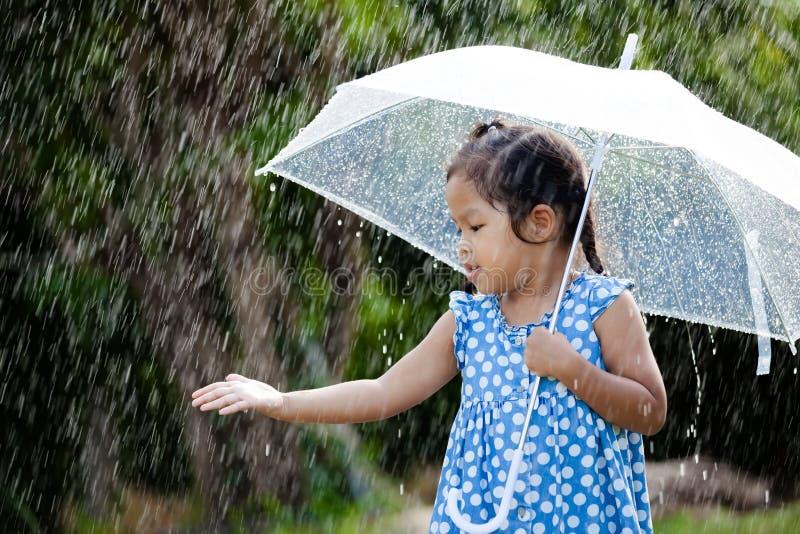 leuk Aziatisch meisje met paraplu in regen stock foto's