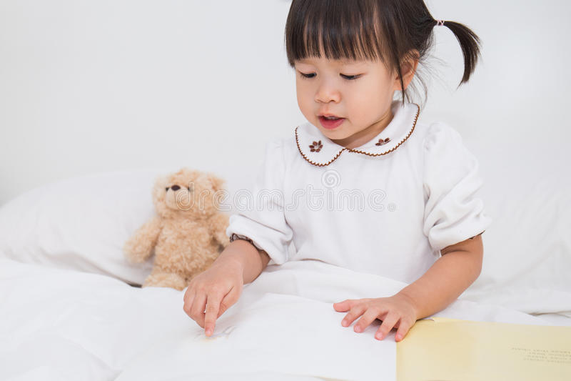 Leuk Aziatisch peutermeisje die een boek lezen stock foto's