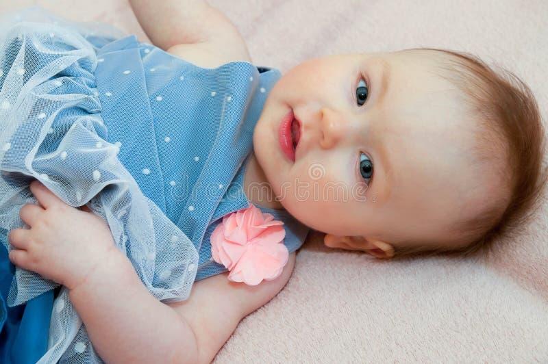 Leuk babymeisje in blauwe kleding met roze bloem royalty-vrije stock foto's
