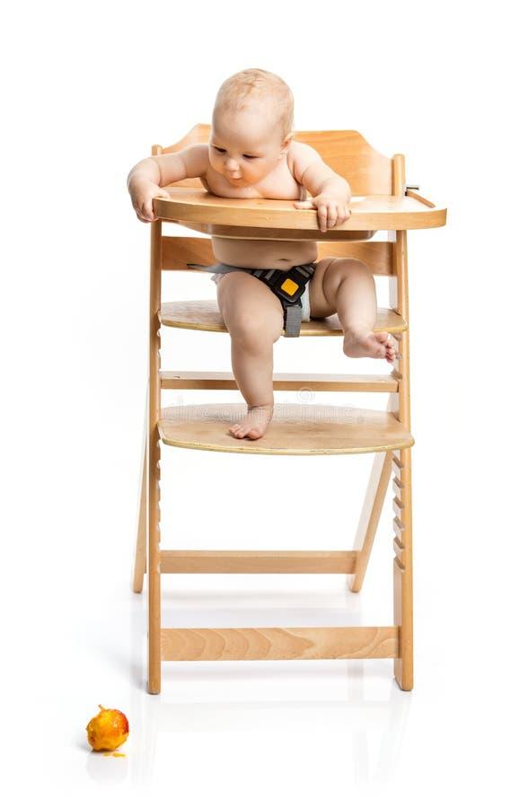 Leuk babymeisje die perzik bekijken die zij terwijl het zitten in hig is gedaald royalty-vrije stock foto's