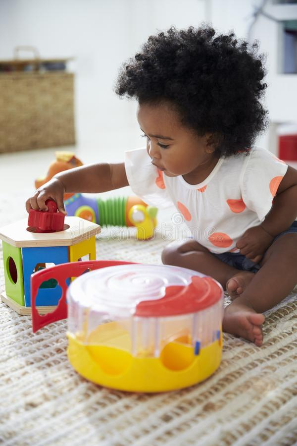 Leuk Babymeisje die Pret in Speelkamer met Speelgoed hebben stock afbeeldingen
