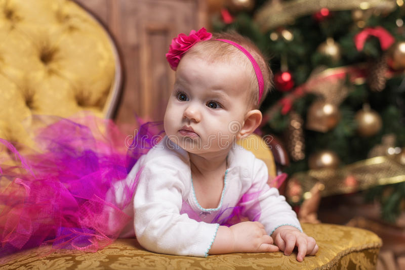 Leuk babymeisje die roze rok en rode hoofdband dragen, die op laag voor Kerstmisboom leggen stock fotografie