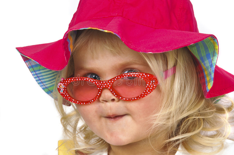 Leuk babymeisje in een rode hoed en zonnebril. royalty-vrije stock foto