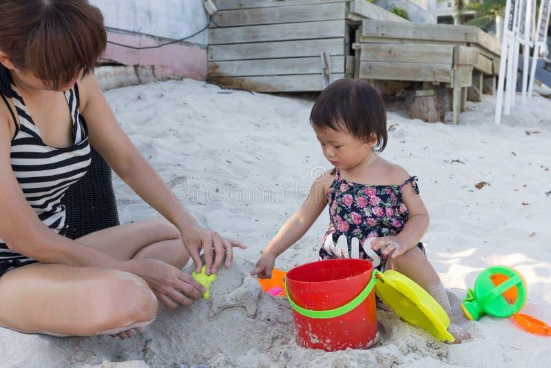 Leuk babymeisje en mooi moeder het spelen zandspeelgoed royalty-vrije stock foto's