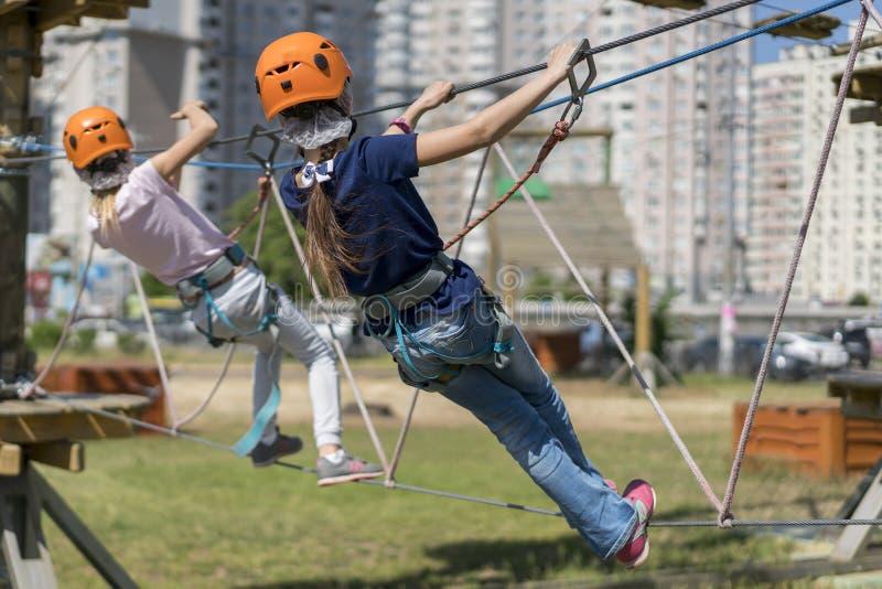 Leuk babymeisje in het beklimmen van toestel op een achtergrond van het kabelpark Weinig mooi meisje beklimt op kabeluitrusting i stock foto