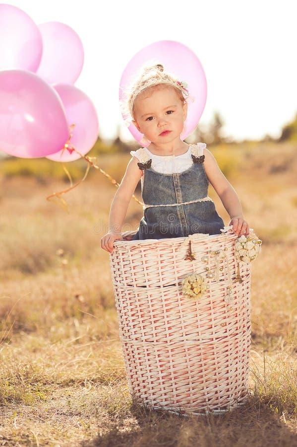 Leuk babymeisje met ballons in openlucht royalty-vrije stock afbeeldingen