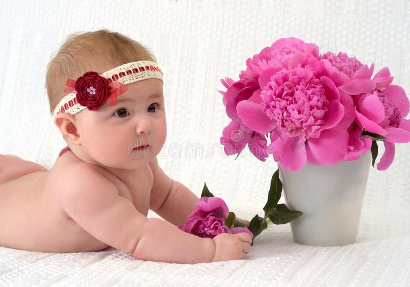 Leuk babymeisje met bloemen stock afbeelding