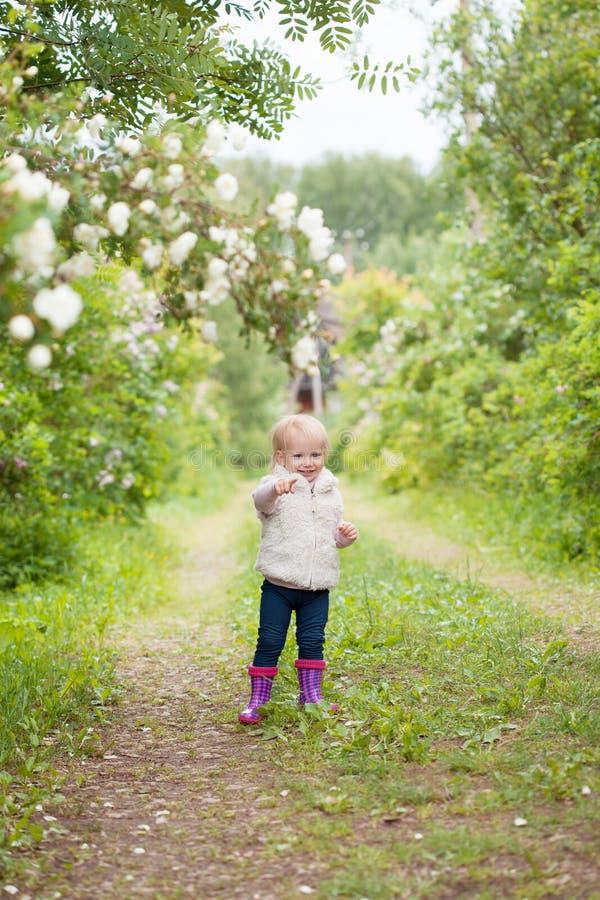 Leuk babymeisje met blondehaar in de bloeiende tuin stock fotografie