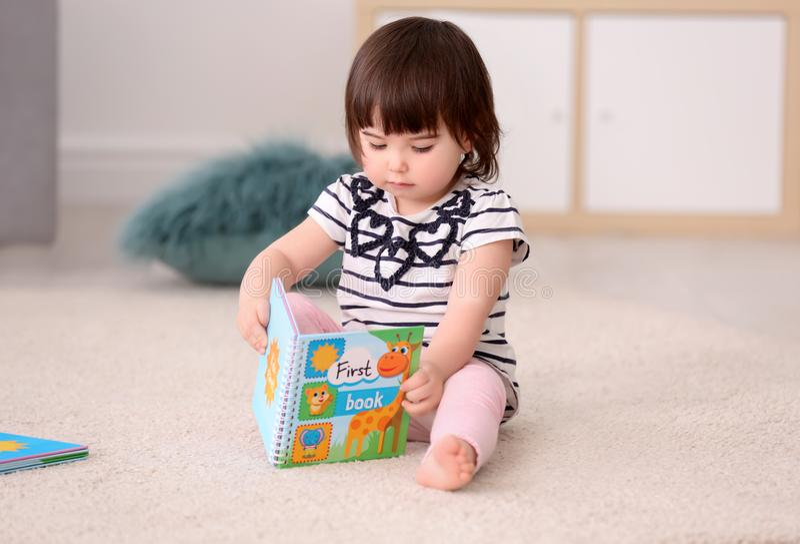 Leuk babymeisje met boekzitting op vloer stock foto