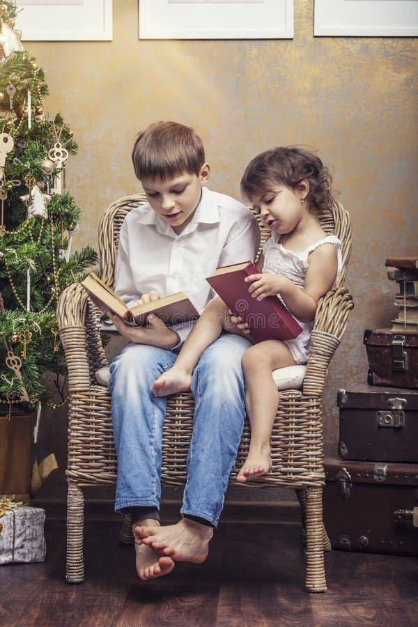 Leuk babysjongen en meisje als voorzitter die een boek in een binnenland lezen stock afbeeldingen