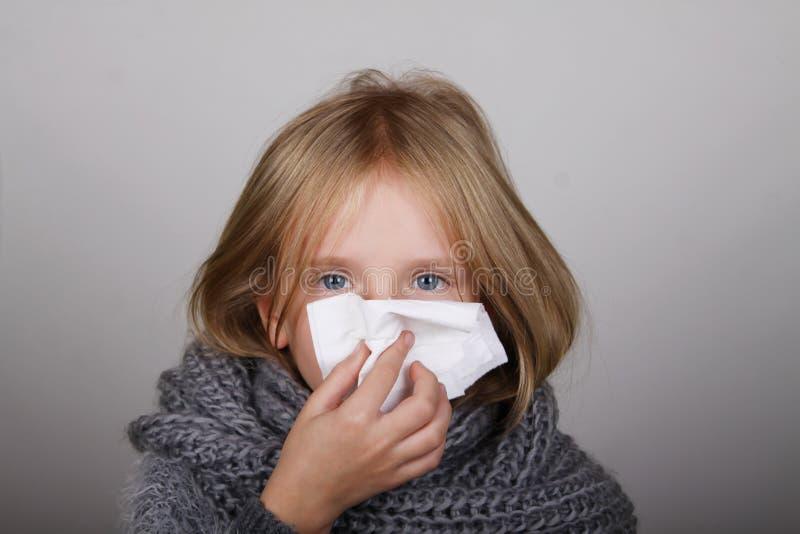 Leuk blond haarmeisje die haar neus met papieren zakdoekje blazen Van de de griepallergie van de kindwinter de gezondheidszorgcon royalty-vrije stock afbeeldingen