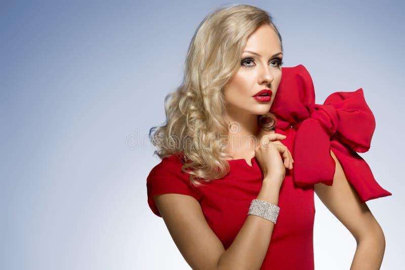Leuk blond jong meisje in rood met grote boog stock afbeelding