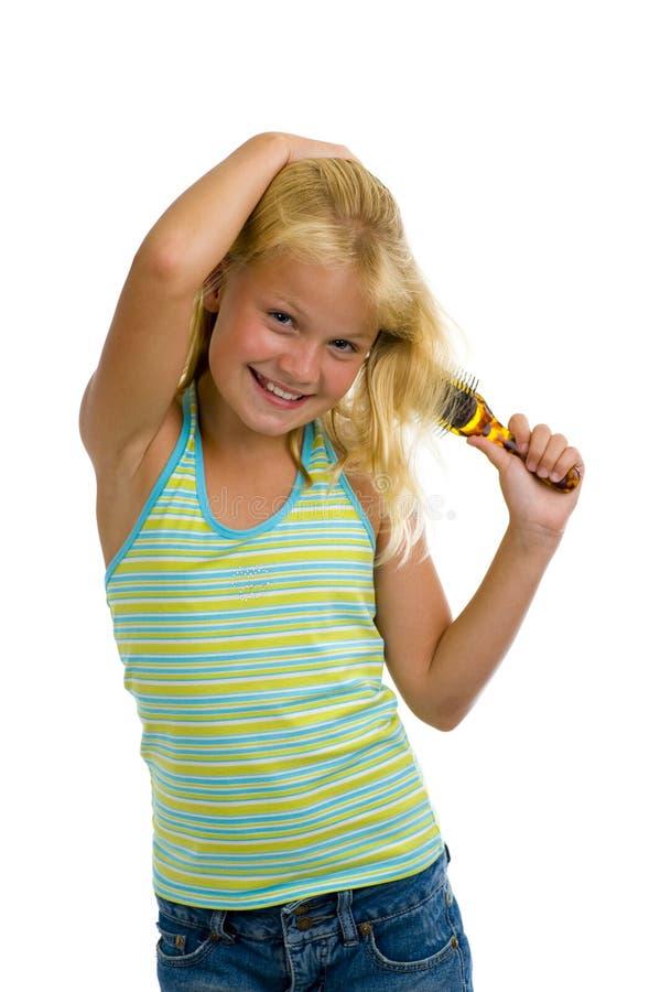 Leuk blond meisje dat haar haar borstelt royalty-vrije stock fotografie