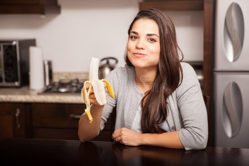 Leuk brunette die een banaan eten royalty-vrije stock afbeeldingen