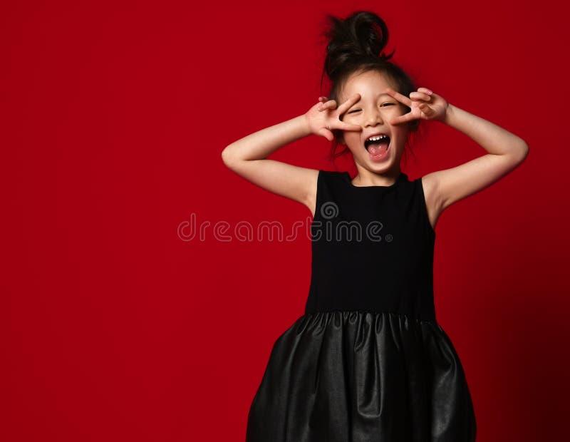 Leuk danst weinig Aziatische meisjesballerina in mooie zwarte kleding tonend vredesteken op rood royalty-vrije stock fotografie