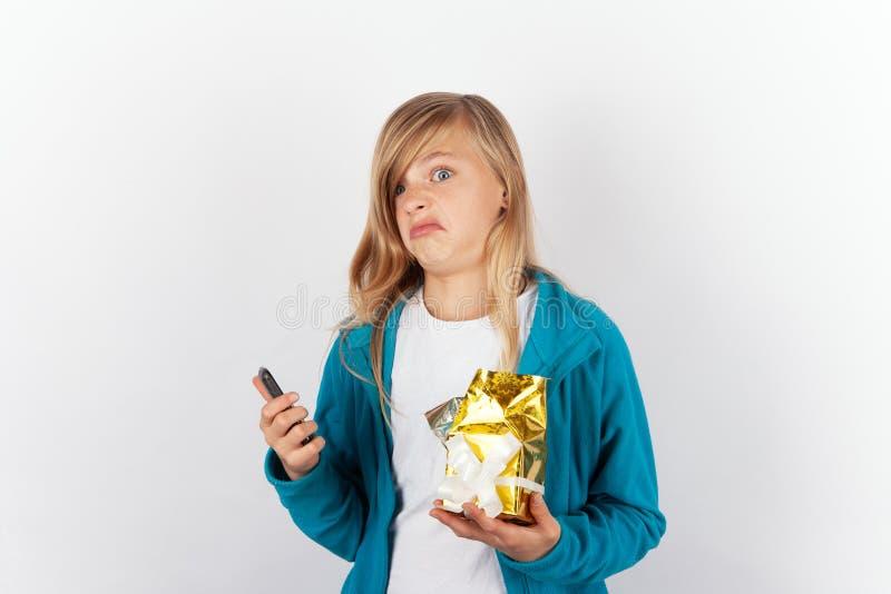 Leuk die meisje zeer met haar Kerstmis of verjaardagsgift wordt teleurgesteld, royalty-vrije stock foto's