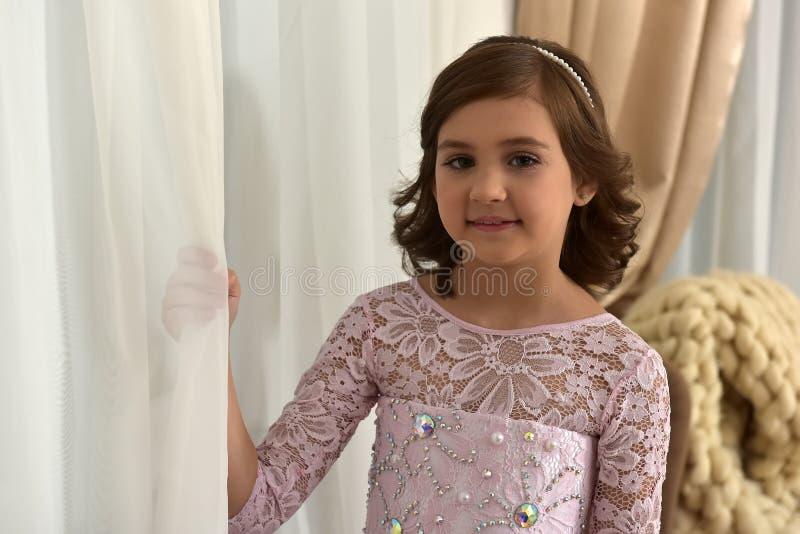 leuk donkerbruin meisje bij het gordijn door het venster royalty-vrije stock foto's