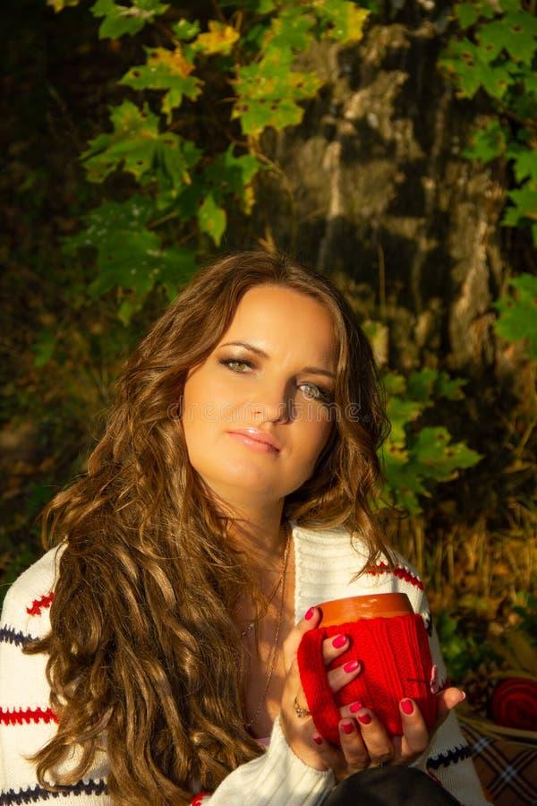 Leuk Donkerbruin meisje, vrouw het drinken koffie in het park van de de herfststad Meisje die van hete drank van rode kop geniete royalty-vrije stock afbeelding