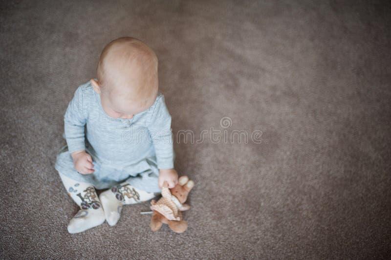 Leuk droevig babymeisje met weinig in hand konijntje Sluit omhoog portret van meisje met stuk speelgoed in grijze kleding royalty-vrije stock afbeeldingen