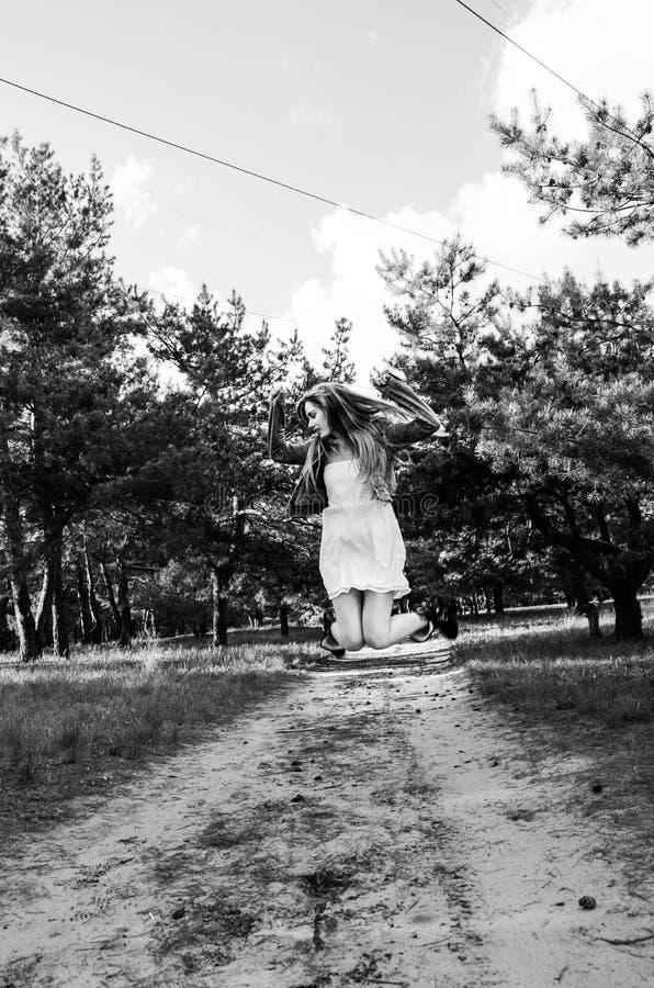 Leuk en vrij jong blond meisje die in witte kleding, jeansjasje en zwarte laarzen op de zandweg springen stock fotografie