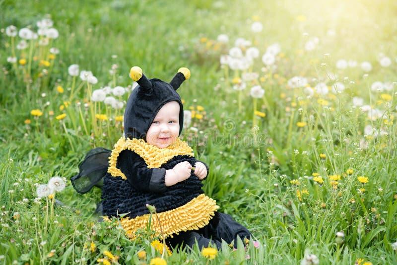 leuk en vrolijk portret van weinig kindzitting in bloeiende bloemen van paardebloem in geel bijenkostuum stock fotografie